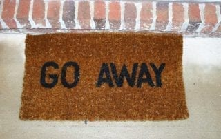 Photo of door mat saying, Go Away.