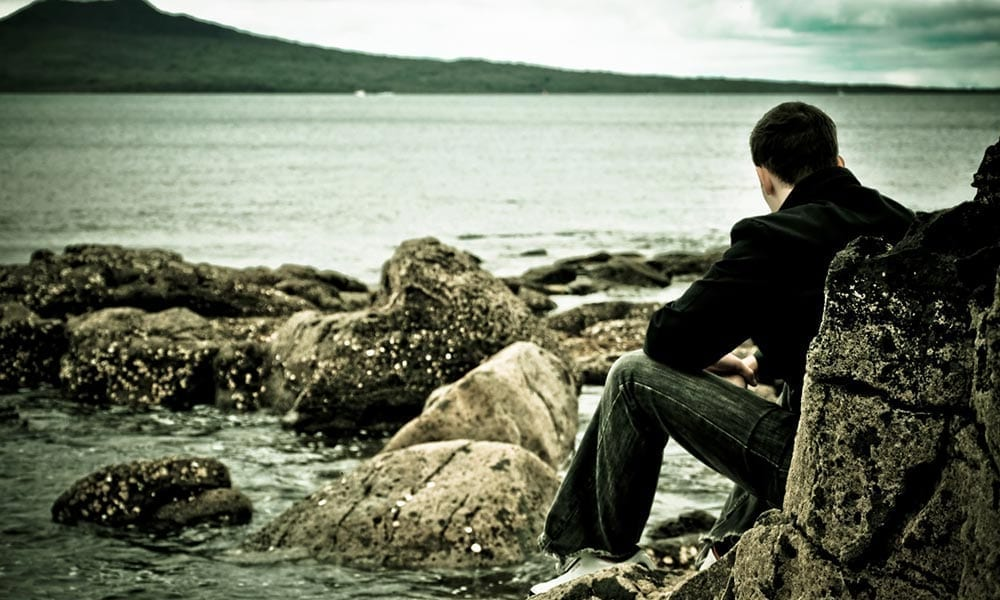 Photo of adolescent sitting near the water, thinking.